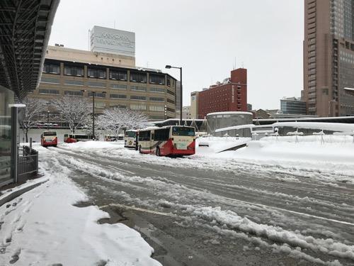 金沢駅東口のバス停留所前の雪景色とシャーベット状の道路