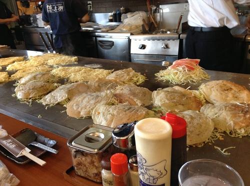鉄板の上に並ぶ20枚ほどの広島風のお好み焼き(お好み焼き・鉄板居食家徳兵衛 広島新幹線店)