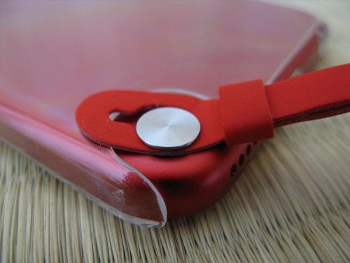 iPod touch 5本体のストラップ(loop)取り付け部分の銀色の円形ボタンの支柱に引っ掛けられたストラップ(loop)(装着途中)