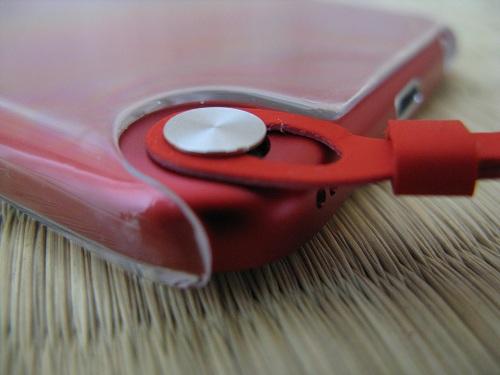 iPod touch 5本体のストラップ(loop)取り付け部分の銀色の円形ボタンの支柱に引っ掛けられたストラップ(loop)(装着完了)