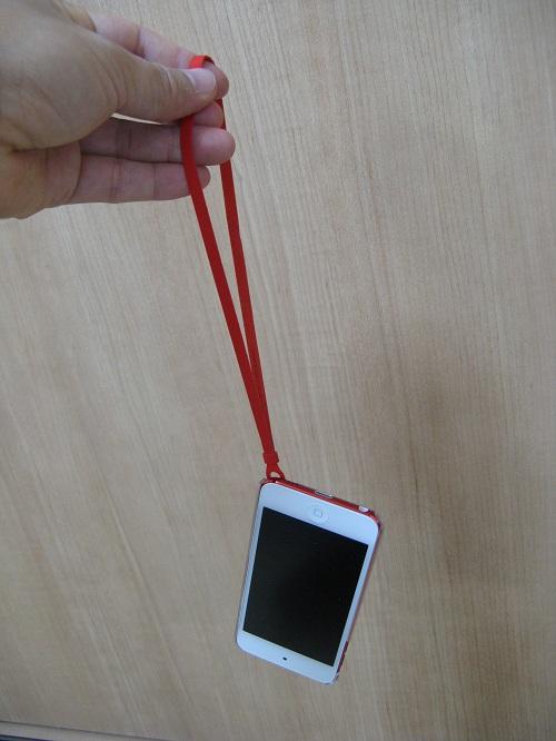 「iBUFFALO iPod touch(2012年発表モデル)専用 3Hハードケース iPod touch loop対応モデル 液晶保護フィルム付」の透明なハードケースを装着したiPod touch 5にストラップ(loop)取り付けて手にぶら下げた様子:iPod touch 5表面側