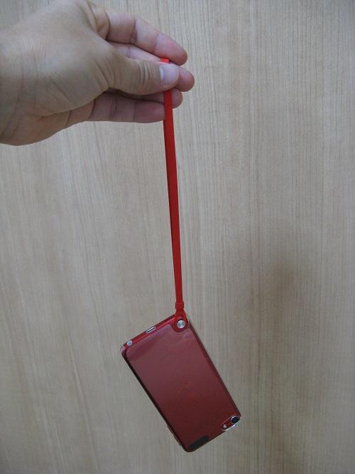「iBUFFALO iPod touch(2012年発表モデル)専用 3Hハードケース iPod touch loop対応モデル 液晶保護フィルム付」の透明なハードケースを装着したiPod touch 5にストラップ(loop)取り付けて手にぶら下げた様子:iPod touch 5裏面側
