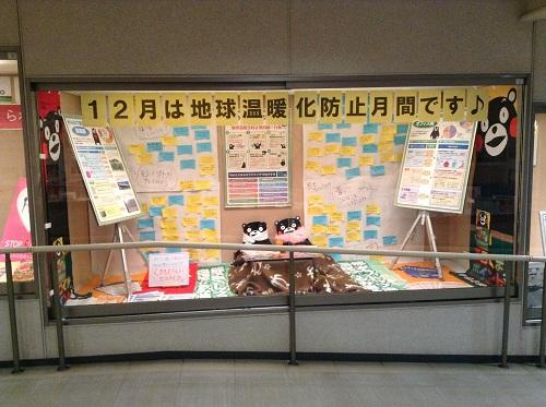 >「12月は地球温暖化防止月間です♪」の告知張り紙とコタツに入っている「くまモン」(熊本県庁の庁舎内にて)