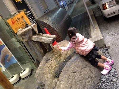 「天然温泉キスケのゆ」の新源泉のお湯をペットボトルに入れる娘
