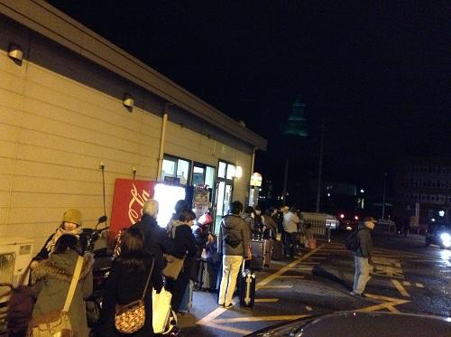 「小倉港 松山行フェリーのりば」のバス停に並ぶ人々