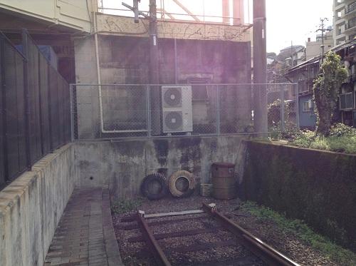 正覚寺下電停の途切れた線路の先にある壁とタイヤ