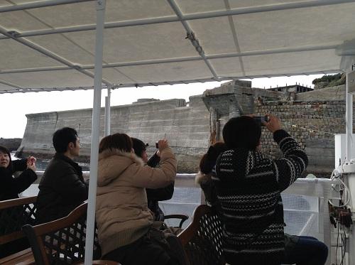 端島(軍艦島)に着岸するマーキュリー(軍艦島上陸・周遊ツアー船)の船上から写真を撮る人々
