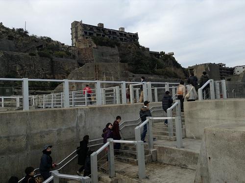 端島(軍艦島)の船着き場から石段を登る人々