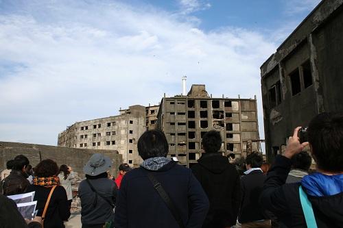 軍艦島の第三見学広場から31号棟(写真左)と30号棟(写真右)のアパートを眺める人々