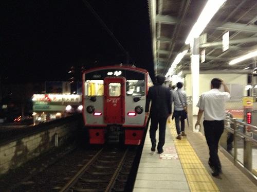 JR別府駅(大分県別府市駅前町)の1番ホームに到着しつつある23時52分発の普通列車に近づく人々