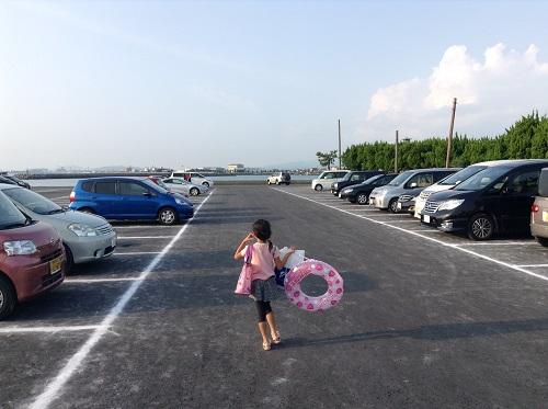 五色姫海浜公園(愛媛県伊予市尾崎)の駐車場(満車ではない)を歩く小学3年生の娘
