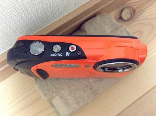 富士フィルムのデジタルカメラ「ファインピックス XP70(オレンジ)」本体(上部・シャッターボタン、動画撮影ボタン、電源ボタン)