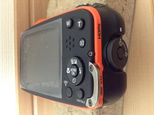 富士フィルムのデジタルカメラ「ファインピックス XP70(オレンジ)」本体(側面・バッテリー、SDメモリカード収納部)
