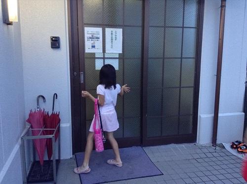 ホテルセレクト愛媛愛南町(住所:愛媛県南宇和郡愛南町広見3367-1)の施設裏口の開き戸を開けようとする娘