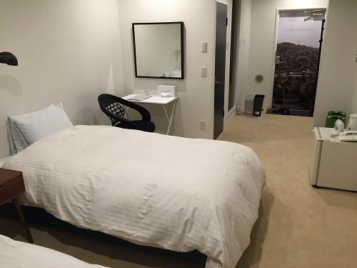 ホテルリッチ(広島県広島市安佐北区可部2-36-1)のツインルームにあるベッドと机、玄関口