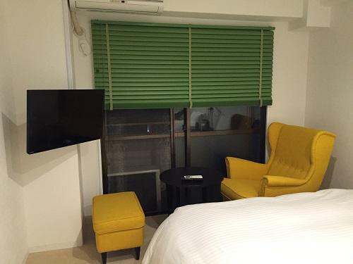ホテルリッチ(広島県広島市安佐北区可部2-36-1)のツインルームにある1人掛けソファーとテーブル、テレビ