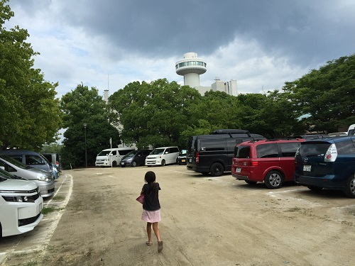 ウェルピア伊予<伊予市都市総合文化施設>(愛媛県伊予市下三谷1761-1)の駐車場、歩く娘