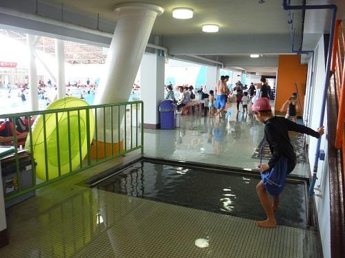 イヨテツスポーツセンターのプールの足洗い場に及び腰で入る小学6年生の娘
