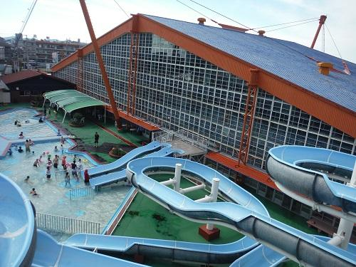 イヨテツスポーツセンター・スパイラルウォータースライダーの頂上から眺めたイヨテツスポーツセンターの建物と屋外プール