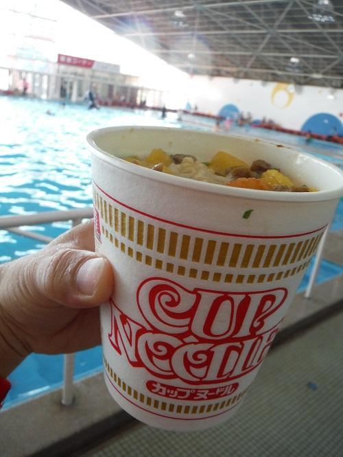 イヨテツスポーツセンターのプールサイドで手に持つ日清カップヌードル