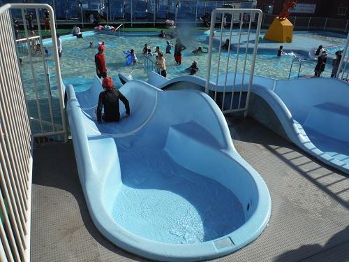 イヨテツスポーツセンターの幼児用プールのウォータースライダーを滑る小学6年生の娘