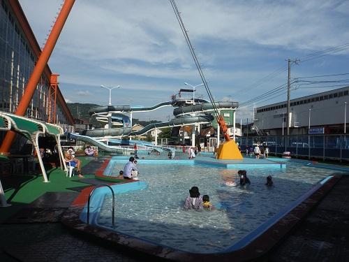 イヨテツスポーツセンターの屋外・幼児用プールと奥に見えるスパイラルウォータースライダー