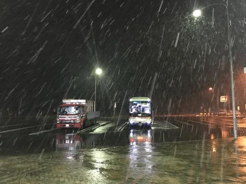 夜が雪降る中、磐越自動車道・西会津PA(パーキングエリア)の駐車場エリアに停車中の仙台行の高速バス「仙台-新潟線(WEライナー)」(JRバス東北)