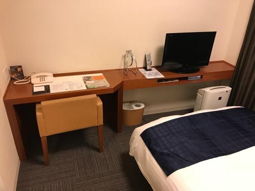 天然温泉 加賀の湧泉 ドーミーイン金沢の禁煙様ダブルルーム室内の机と椅子とテレビ