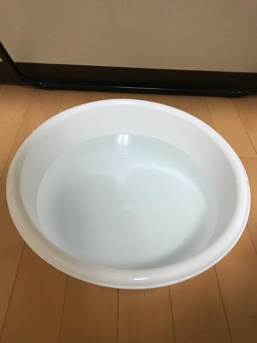 100円ショップ・ダイソーで購入した洗い桶(丸)33cm、容量7リットルにお湯を入れて部屋の床に置いた様子