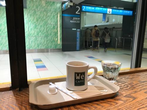 We CAFFE エキュート大宮店のカウンターテーブルに置いたホットコーヒーと水、窓の向こうに見える京浜東北線の標識