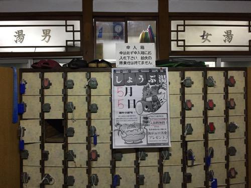 東京都荒川区の銭湯・玉の湯の玄関にある傘入箱とガラス窓に記載された男湯と女湯の表示