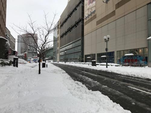 ドーミーイン金沢前の歩道を覆う雪とシャーベット状の道路(右横の建物は金沢フォーラス)
