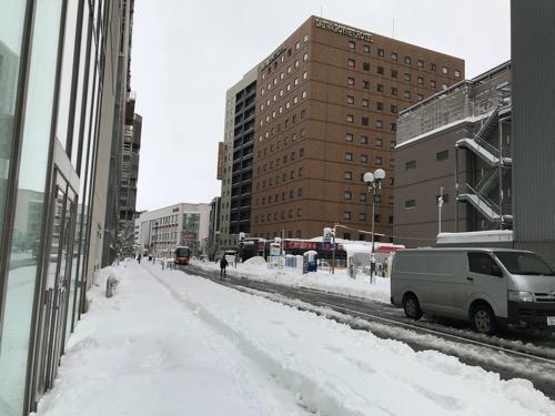 金沢フォーラス前の歩道の上にできた雪道とドーミーイン金沢とダイワロイネットホテル金沢