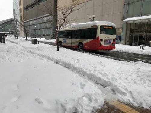 ドーミーイン金沢前の歩道を覆う雪と去りゆく路線バス