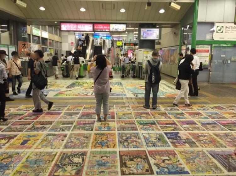 JR亀有駅改札口前の床に貼られたこち亀コミックスの表紙集