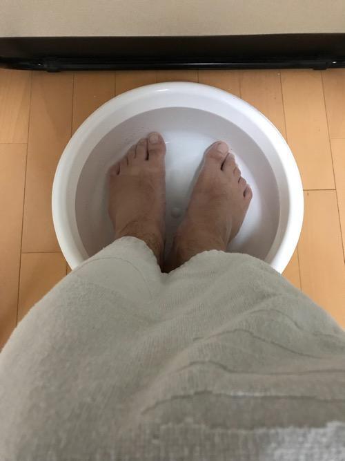 100円ショップ・ダイソーで購入した洗い桶で足湯をしている様子