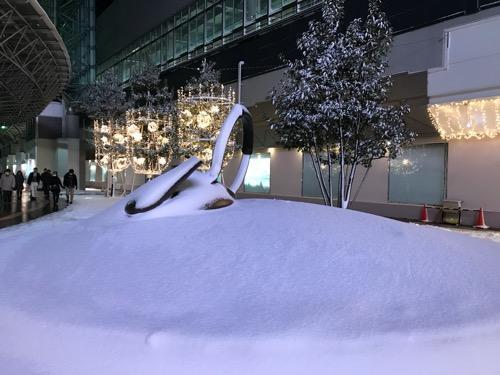 雪に埋もれるやかん - 背景:金沢フォーラス前(金沢駅東口)