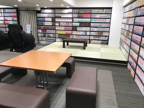 新潟第一ホテルのコミックルームとテーブルと椅子とマッサージチェア