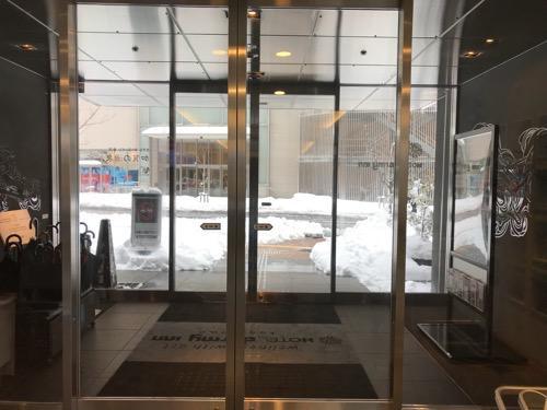 ドーミーイン金沢の出入口の自動ドアの向こうに見える雪景色