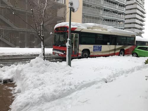 ドーミーイン金沢の出入口前の雪景色と路線バス
