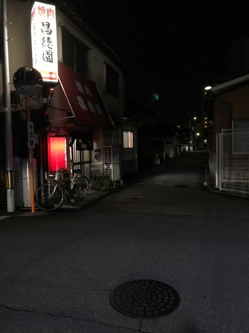 金沢市の市章が入ったマンホールの蓋と焼肉 昌徳園前の夜の道路の風景