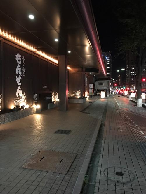 石川県金沢市の金沢シティホテル1階の飲食店・もんぜん前の歩道と一体化したマンホールの蓋と周辺の夜間の様子