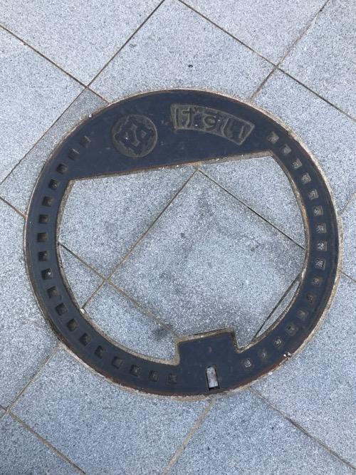 福井県福井市の「げすい」と書かれた周辺の道の石模様が付いたマンホールの蓋