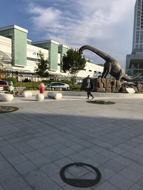 福井県福井市の「げすい」と書かれた周辺の道の石模様が付いたマンホールの蓋の周囲の様子 - JR福井駅西口駅前広場の恐竜など