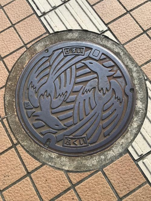 福井県福井市のシンボル・不死鳥が描かれ、「げすい ふくい」と書かれたマンホールの蓋