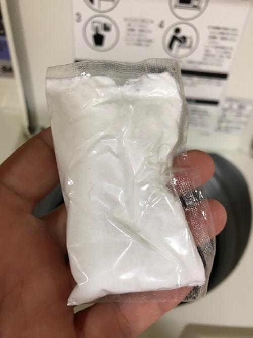 コインランドリー用無リン洗剤「ゲンブ クリーン20」の洗剤が入った袋を手の平に乗せた写真