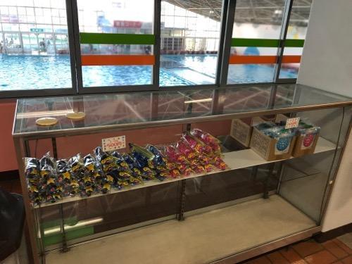 イヨテツスポーツセンター2階の受付窓口のすぐ近くにある水中眼鏡などの販売ケースと2階から眺めた室内プール