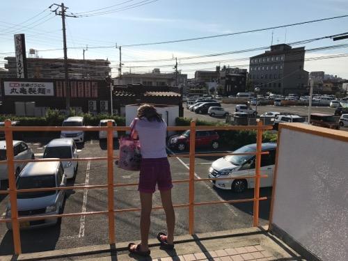 イヨテツスポーツセンター2階の外階段の手すりから景色を眺める小学6年生の娘