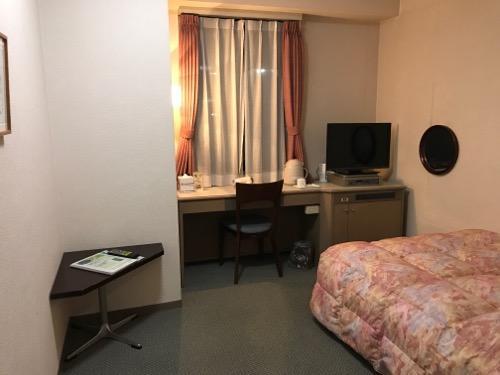 ホテルエコノ金沢駅前のシングルルームの机、椅子、ベッド