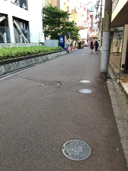 千葉県松戸市のマンホールの蓋(コアラの絵柄・色付けなし)と周辺風景(松戸駅東口周辺)